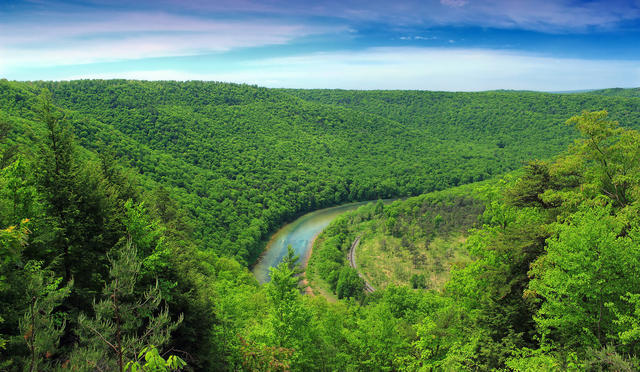 A small river winding through a landscape of low mountains covered in lush, green forests.